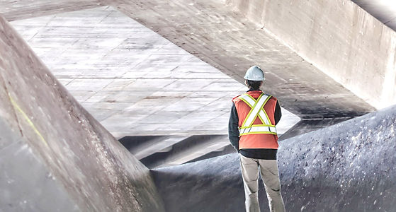 Construction worker looking at a worksite covered in pavement