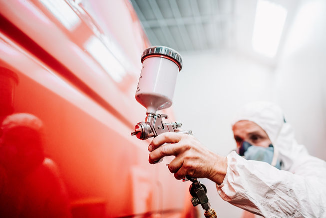 close up of worker painting a red car in a special garage, wearing a white costume.jpg