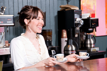 Woman standing next to a espresso machine holding 2 cups of coffee and smiling.