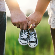 adoptive couple holding baby shoes
