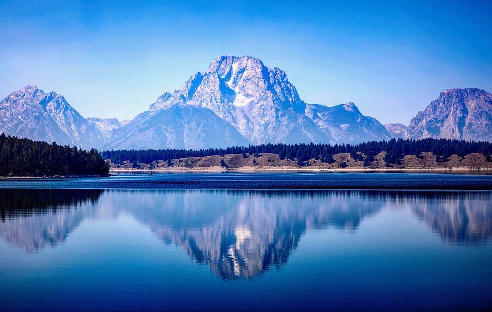 Mount Moran towers above the calm waters of Jackson Lake. Grand Teton National Park.