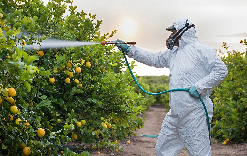 A worker requires a hazmat suite to apply pesticide to food we are expected to eat.