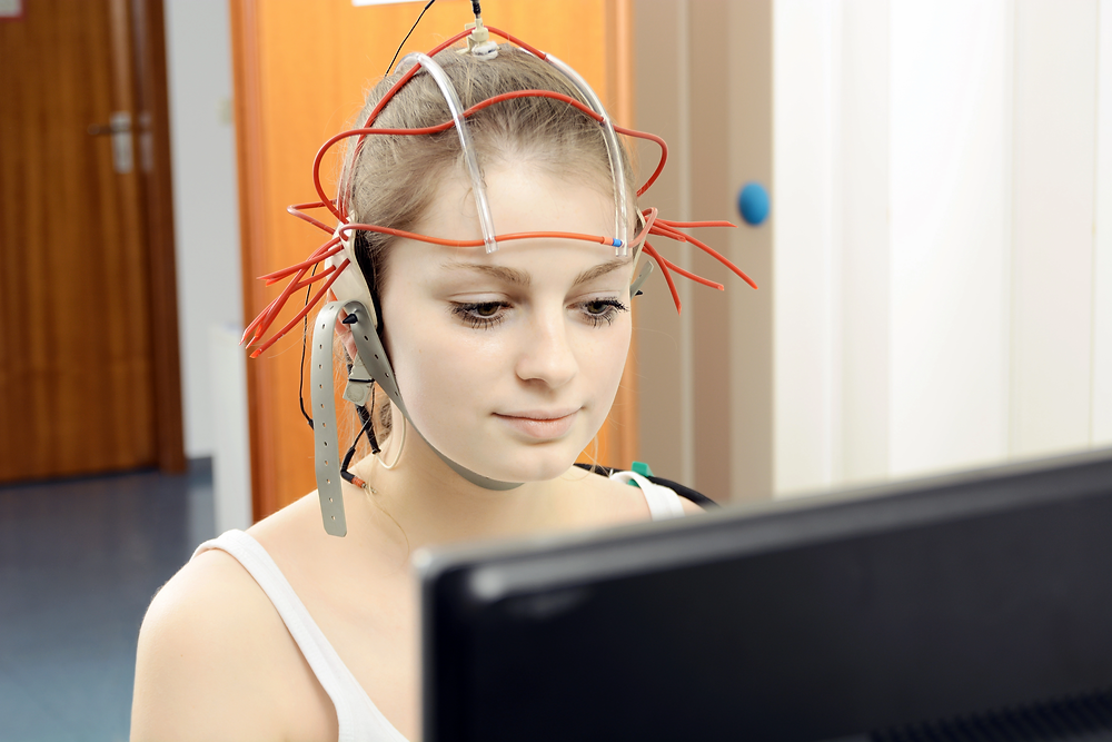 A patient actively concentrates on a screen to drive a specific brainwave response.
