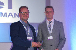 Randall Barney (right), WTA Membership Director hands the award to Guido Neumann, Managing Director of CETel