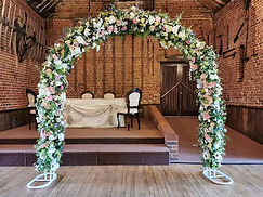 7ft Artificial Floral Wedding Arch. Filled with a variety of blush/pink flowers and greenery to create a stunning full backdrop. We can also add in your accent colours to match your theme.