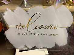 """""""Welcome to Our Happily Ever After"""" Acrylic Sign With White Painted Back and Gold Lettering"""