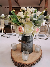 • 8x Milk churns filled with floral centrepieces • 8x Mirror base in silver, gold, rose gold or log slice • 2x Candle votives with LED Candles for each table • 1x Top table / ceremony table artificial floral spray