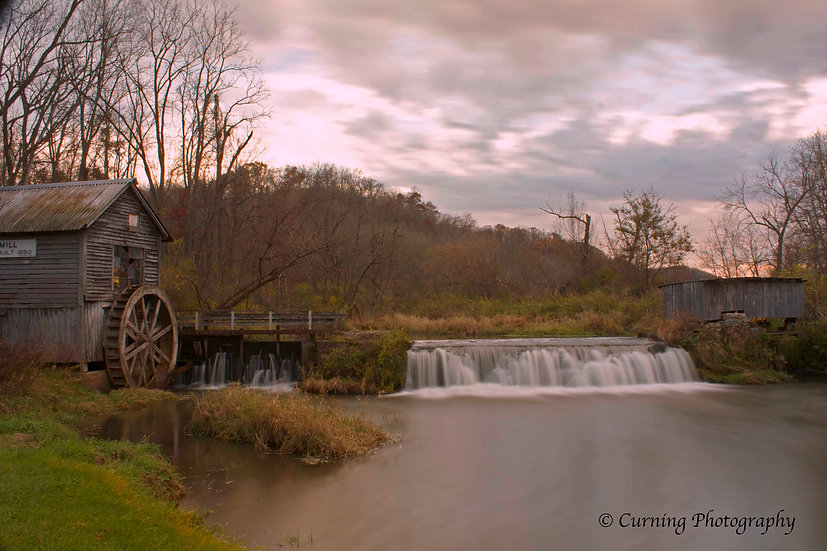 photograph of an old rural mill with a waterfall at sunset