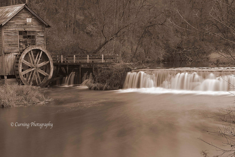 photograph of a old rural mill with a waterfall in sepia tone