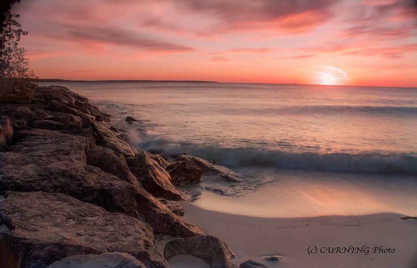photograph of water crashing on rocks at sunrise