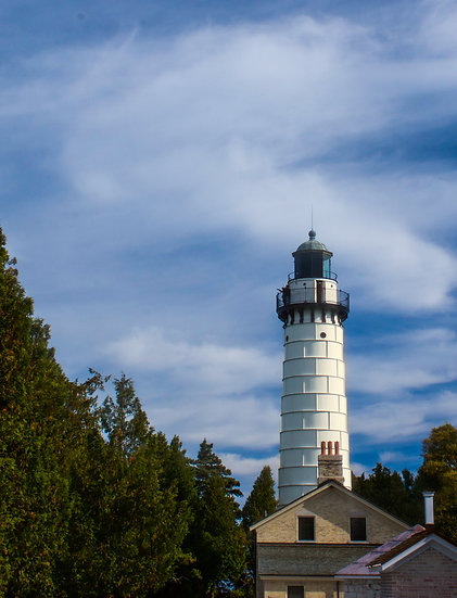 photograph of a white light house against a partly cloudy sky
