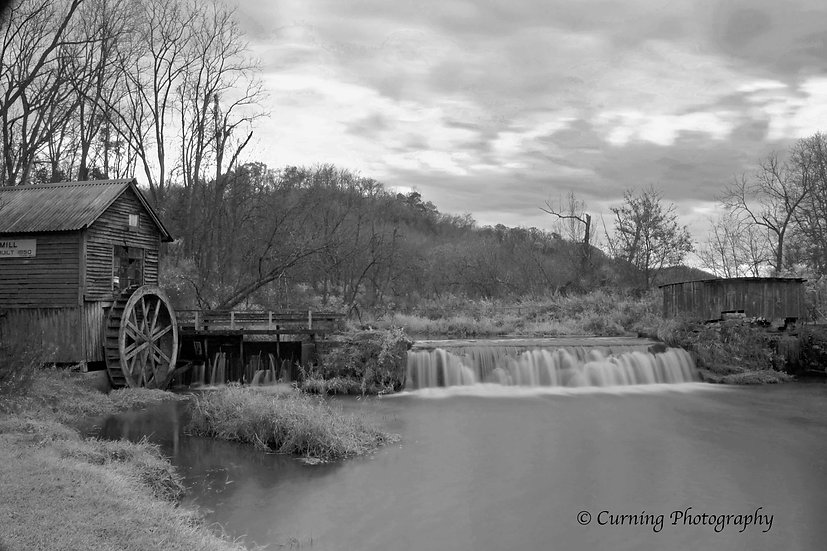 Photograph of a rural old mill with a waterfall and trees in black and white