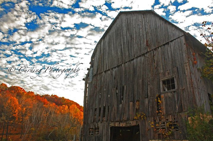 Photograph of an old unpainted barn with fall trees and clouds in the background