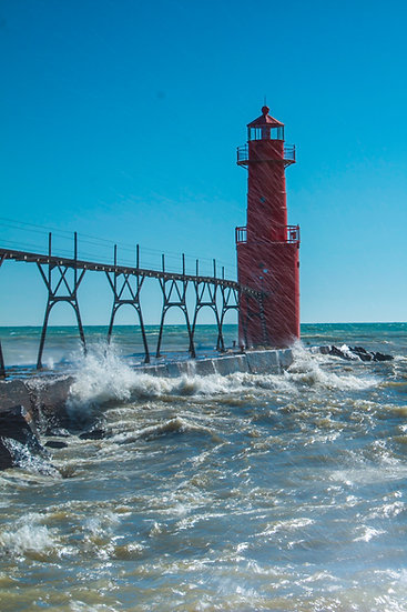 photograph of water spraying across a red light house on the water