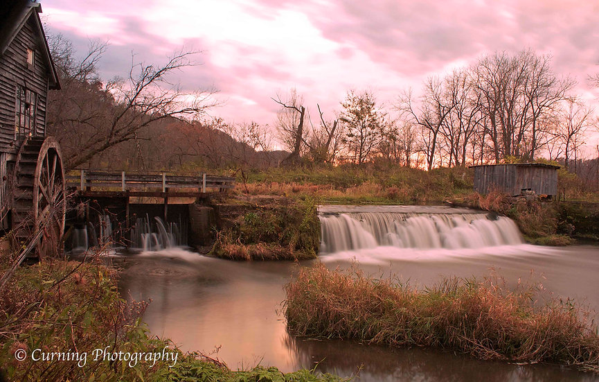 photograph of a old rural mill with a waterfall at sunset in the fall