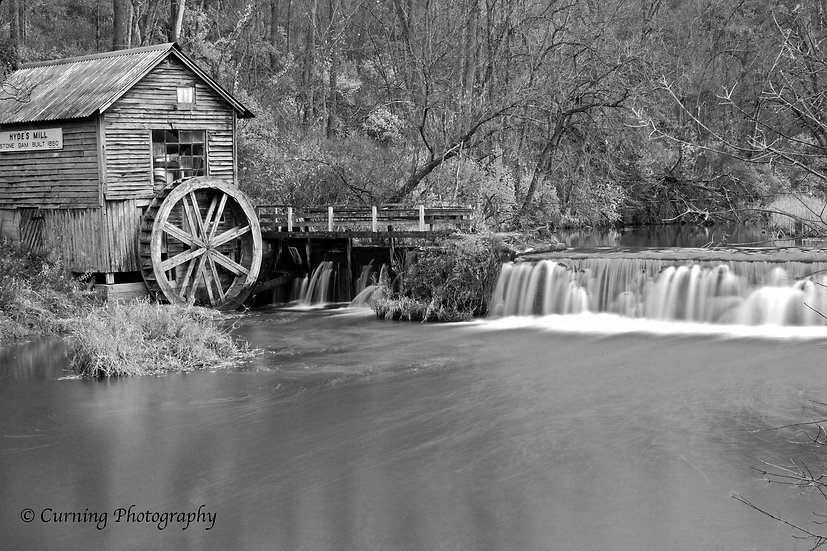 Photograph of a rural old mill with a waterfall and trees in the background in black and white infrared