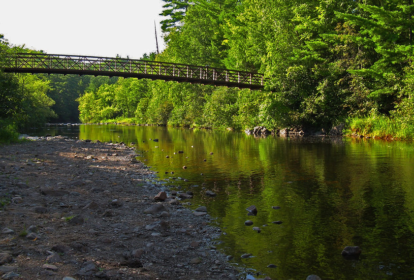 Photograph of small wooden bridge into the woods over a river and a rocky shore