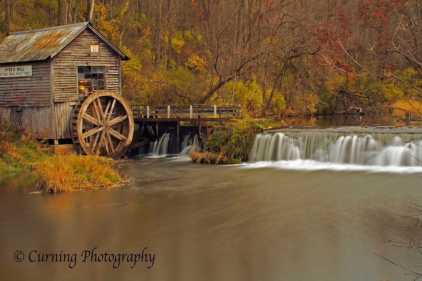 photograph of a rural old mill with a waterfall in the fall with lots of trees in the background