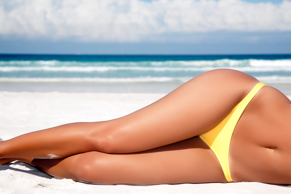Lady with tanned legs lying on beach