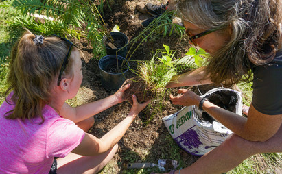 kid planting with mentor