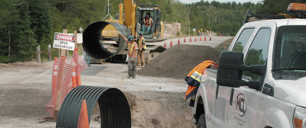 A construction crew working at a highway culvert installation