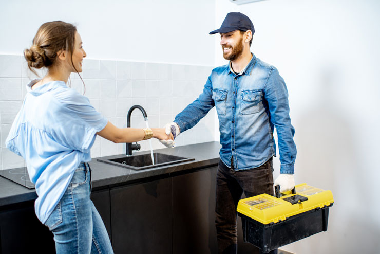 Handy man having a deal with young woman client after the repairment on the kitchen