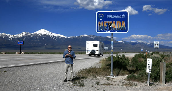 Jack at the Nevad border, holding up his Loneliest Road Survival Passport