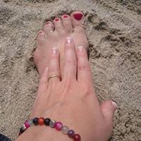 Manicured foot and hand in sand