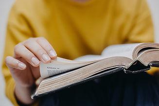 Woman yellow shirt turning bible page.jpeg