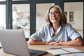Smiling stylish mature middle aged woman sits at desk with laptop, portrait. Happy older s