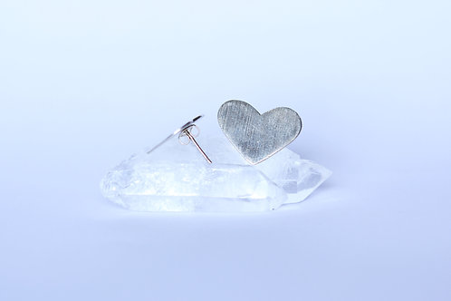 large oversized heart studs earrings in brushed sterling silver on crystal and white background