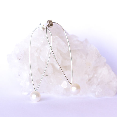 Sterling silver and pearl stud drop earrings elegant handcrafted jewelry on crystal background