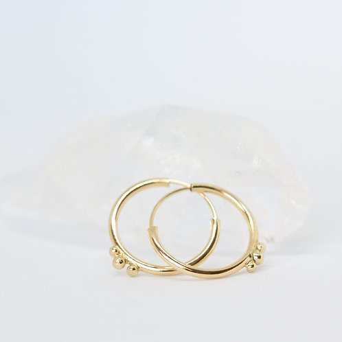 minimal gold hoop earrings with gold details with a white and crystal background, handcrafted jewelry from Jerusalem