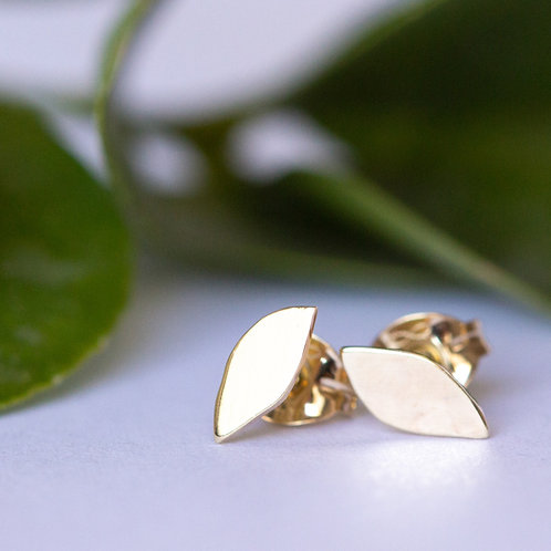 Tiny gold leaf studs earrings handcrafted in Jerusalem with leaves in background