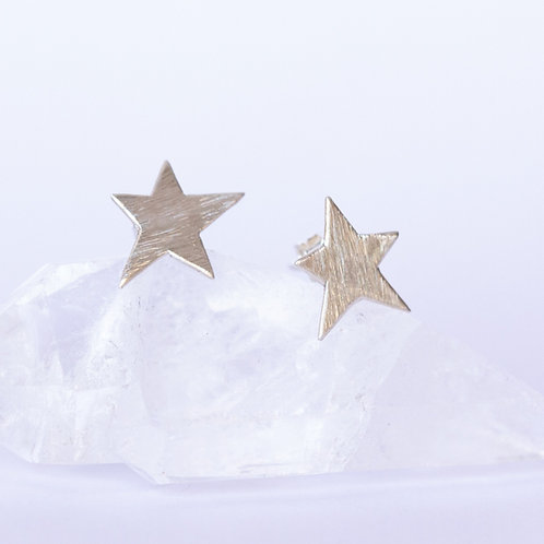 Star stud earrings in textured brushed sterling silver on a crystal and white background unique handcrafted jewelry