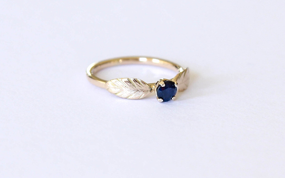 Unique handcrafted sapphire and gold engagement ring with feather detail