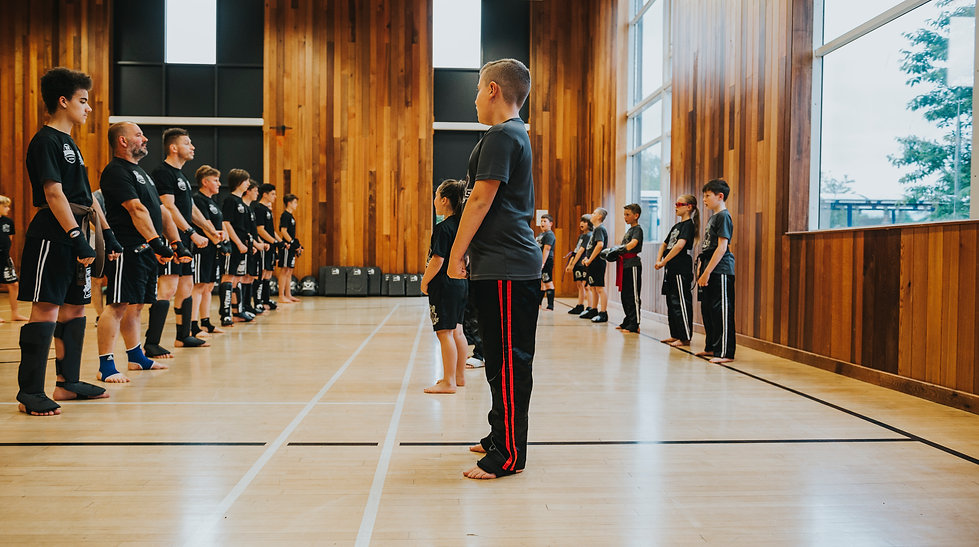 junior kickboxing students wait in line to begin their lesson
