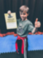 JUNIOR KICKBOXING STUDENT IN KIRKBY WITH HIS RED BELT & GRADING CERTIFICATE
