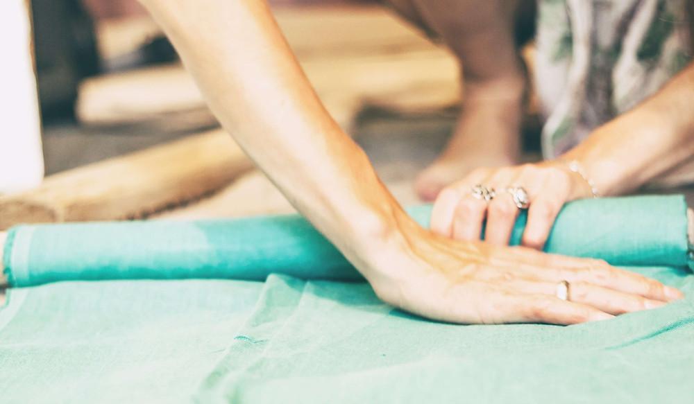 Sebuah tangan menghaluskan secarik kain hijau