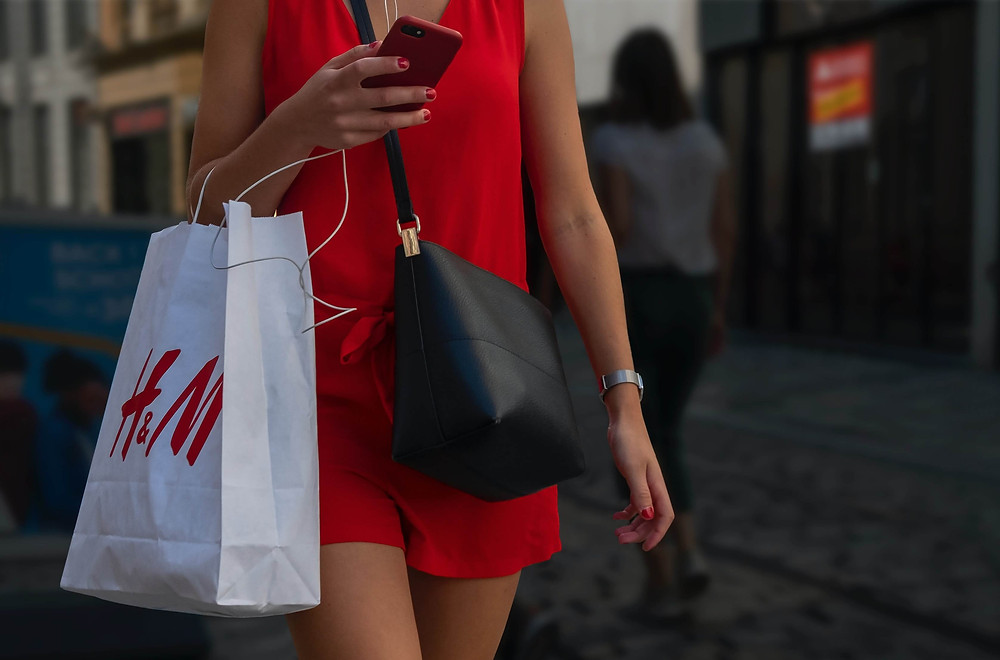 A woman wearing a red jumpsuit carrying an H&M shopping bag and a black bag