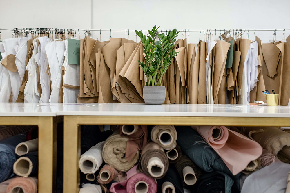 A store with racks of white and brown clothes