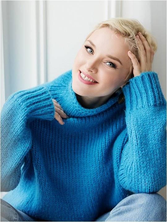 Kaunis nainen sinisessä villapaidassaan.
