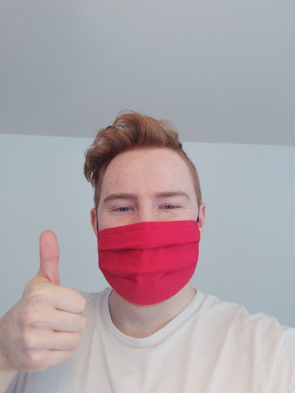 selfie of a man wearing a red mask doing a thumbs up
