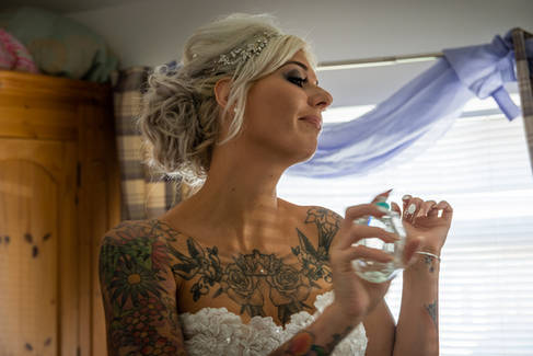 A bride applying perfulme to her wrist.
