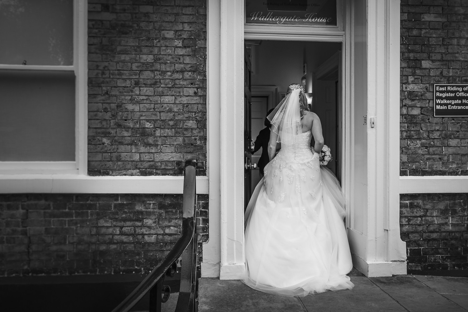 A bride to be enters Beverley Registry Office. We see the back of her dress and veil.