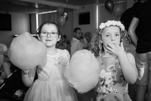 Two girls enjoy candyfloss from a cart at the wedding reception.