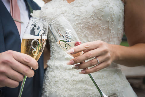 """The bride and groom hold matching """"Mr"""" and """"Mrs"""" champagne flutes at The Potting Shed, Beverley."""