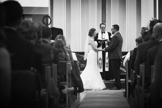 A bride and groom are shown reciting their vows. We view them down the aisle in the church.