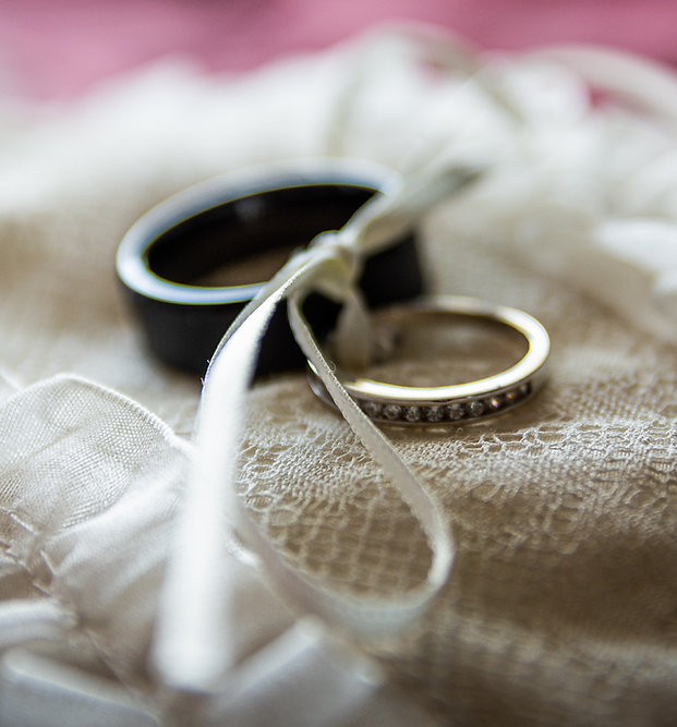 Two wedding rings are bound together with an ivory ribbon. The rings sit atop a lace pillow.