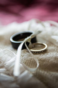 Two wedding rings are shown bound by a piece of ribon and sat atop a lace pillowcase.